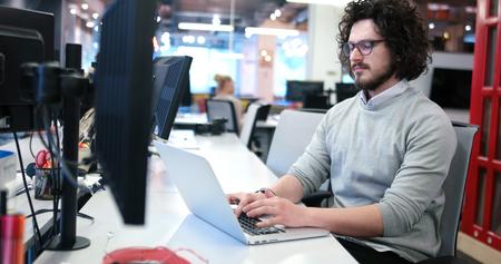 Jeune entrepreneur entrepreneur indépendant travaillant à l'aide d'un ordinateur portable dans l'espace de coworking Banque d'images - 82522216