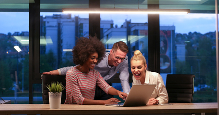 african american woman: Multiethnic startup business team on meeting in modern night office interior brainstorming, working on laptop