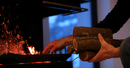Closeup of human hands at fireplace making fire Stock Photo