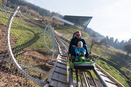 Excited father and son enjoys driving on alpine coaster Stock Photo