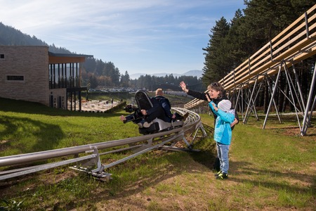Happy family enjoys driving on alpine coaster Stock Photo