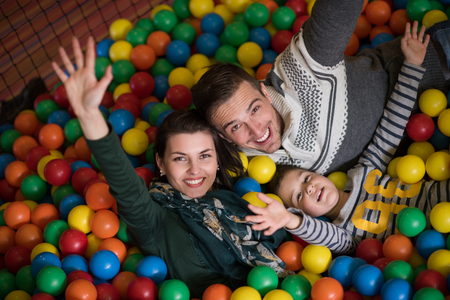 Happy young parents are playing with their kids at pool with colorful balls in a children's playroom Stockfoto