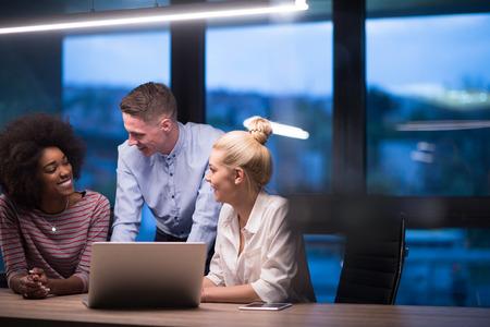 Multiethnic startup business team on meeting in modern night office interior brainstorming, working on laptop Reklamní fotografie - 82630972