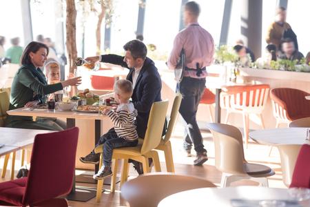 Los padres jóvenes disfrutando de la hora del almuerzo con sus hijos en un restaurante de lujo