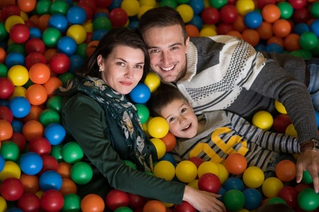 Happy young parents are playing with their kids at pool with colorful balls in a children's playroom photo