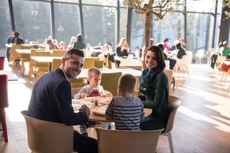 Young parents enjoying lunch time with their children at a luxury restaurant photo