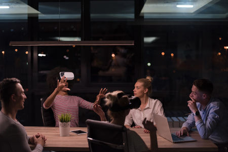 virtual reality simulator: Multiethnic Business team using virtual reality headset in night office meeting  Developers meeting with virtual reality simulator around table in creative office.