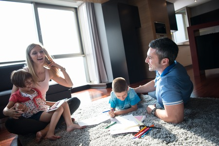 Happy Young Family Playing Together at home on the floor using a tablet and a childrens drawing set Banco de Imagens