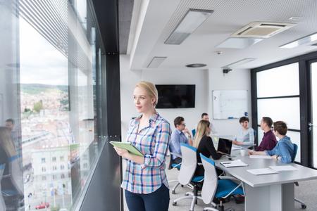 창에서 회사 사무실에 디지털 태블릿을 사용 하여 비즈니스 우먼