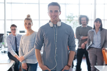オフィスでバック グラウンドで同僚と若い casuall ビジネスマンを笑顔の肖像画 写真素材