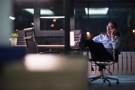 Joven empresario utilizando teléfono móvil mientras trabajaba en la computadora portátil en la noche en la oficina oscura. Foto de archivo - 82832974