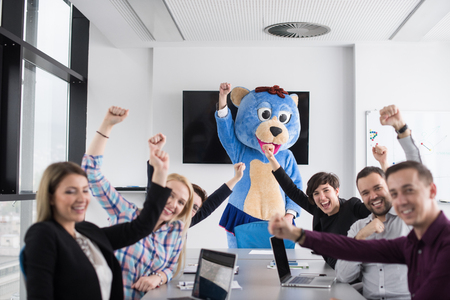 Boss dresed as teddy bear having fun with bussines people in modern corporate office photo