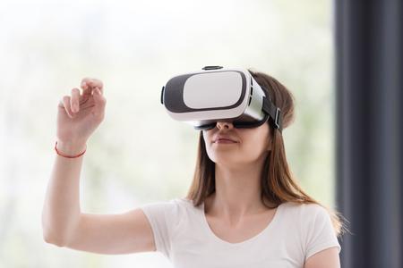 Glimlachende gelukkige vrouw krijgt ervaring met gebruik van VR-headsetbril virtuele realiteit thuis Stockfoto