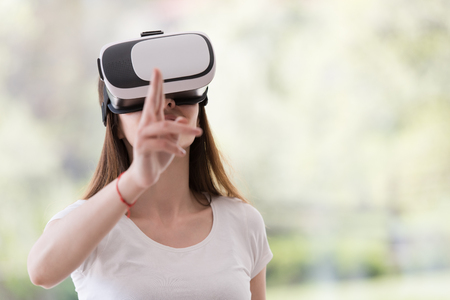 virtual reality simulator: Smile happy woman getting experience using VR-headset glasses of virtual reality at home