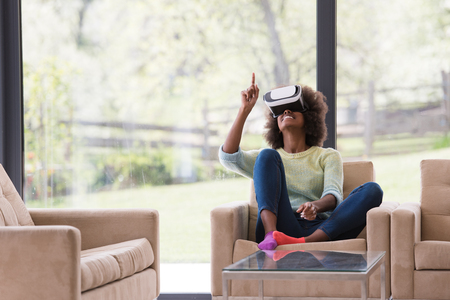 26ad35bdc8a Happy african american girl getting experience using VR headset glasses of virtual  reality at home