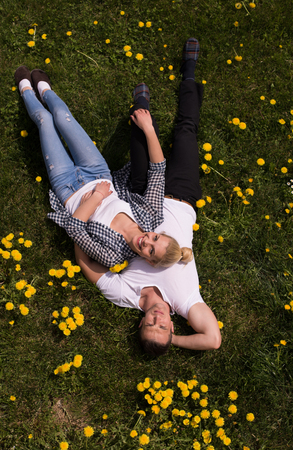Overhead view of young man and woman lying on the grass, Top view of relaxed young couple lying down on meadow. Stock Photo