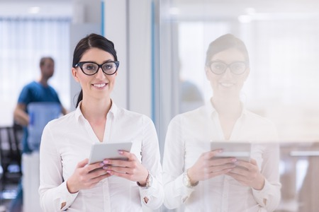 Jolie femme d & # 39 ; affaires en utilisant la tablette en utilisant un intérieur de bureau de démarrage Banque d'images - 84853382