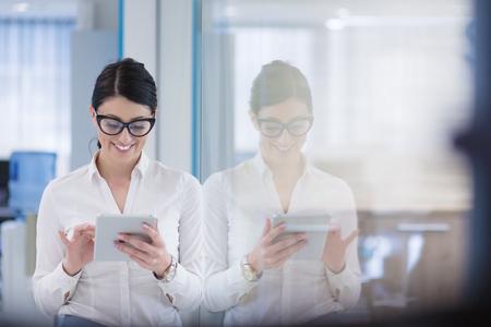 Jolie femme d & # 39 ; affaires en utilisant la tablette en utilisant un intérieur de bureau de démarrage Banque d'images - 84851325
