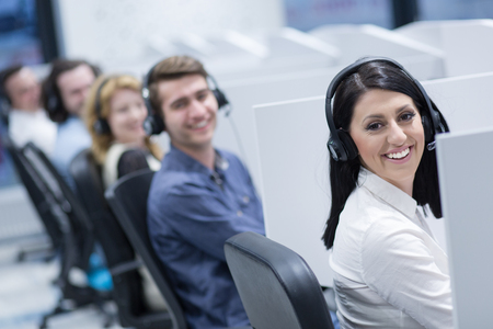grupo de jóvenes empresarios con auriculares trabajando y dando beneficios a los clientes en una oficina de call center Foto de archivo