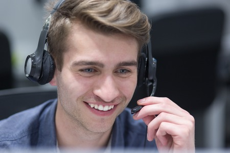 young smiling male call centre operator doing his job with a headset Stockfoto