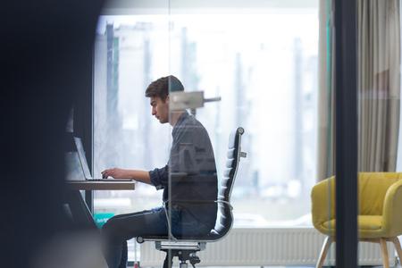 Jeune entrepreneur pigiste travaillant dans un ordinateur portable dans coworking espace Banque d'images - 84851315