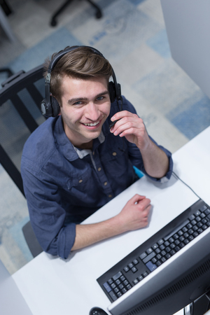 top view of a young smiling male call centre operator doing his job with a headset Stock Photo