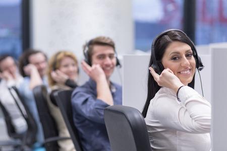 ヘッドセット作業、支援コール センター オフィスの顧客に持つ若いビジネス人々 のグループ