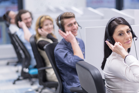 group of young business people with headset working and giving support to customers in a call center office Imagens - 84909175