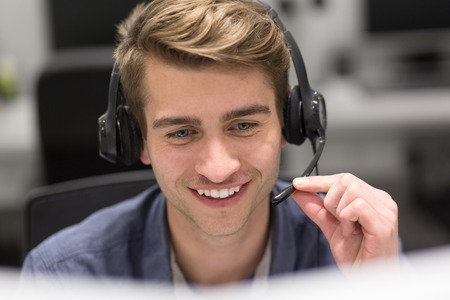 young smiling male call centre operator doing his job with a headset Banque d'images