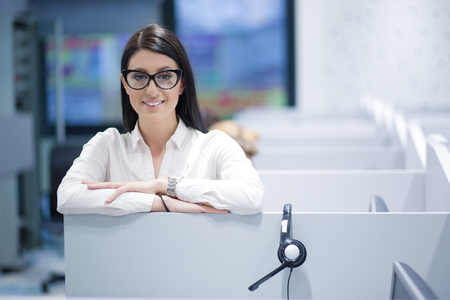young smiling female call centre operator doing her job with a headset Stock Photo