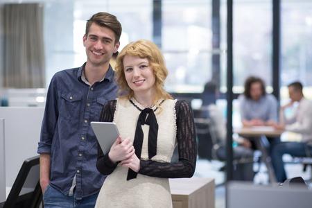 Zakenmensen die tabletcomputer gebruiken tijdens de voorbereiding voor de volgende collega's op de achtergrond, die ideeën bespreken bij het opstartkantoor