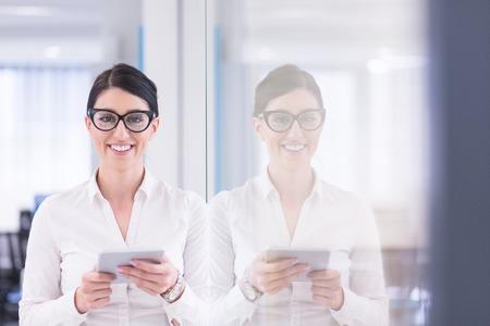 Jolie femme d'affaires utilisant la tablette devant le démarrage Office Interior Banque d'images - 84794185