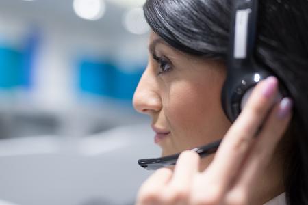 Jonge lachende vrouwelijke call center operator doet haar werk met een headset Stockfoto
