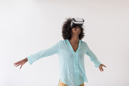 Happy african american girl getting experience using VR headset glasses of virtual reality, isolated on white background Stock Photo