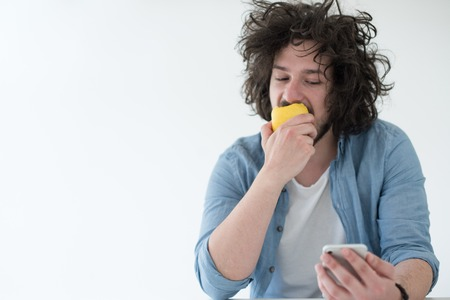 Handsome casual young man eating apple and using a mobile phone at  home