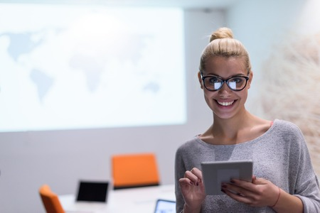 young female entrepreneur working on digital tablet in night office Stock Photo