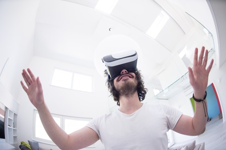 happy man getting experience using VR-headset glasses of virtual reality at home Stock Photo