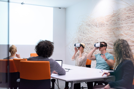 startup Business team using virtual reality headset in night office meeting  Developers meeting with virtual reality simulator around table in creative office. Banco de Imagens