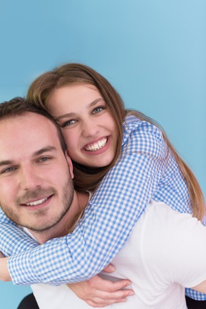 happy young man piggybacking his girlfriend isolated on blue background