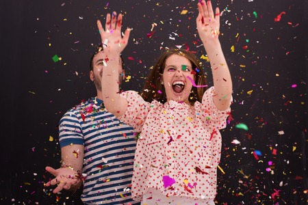 handsome young couple celebrating new year and chrismas party while blowing confetti decorations to camera isolated over gray background Stock Photo