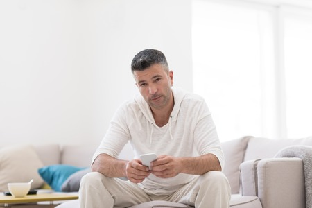 Handsome casual young man using a mobile phone at luxurious home Stock Photo