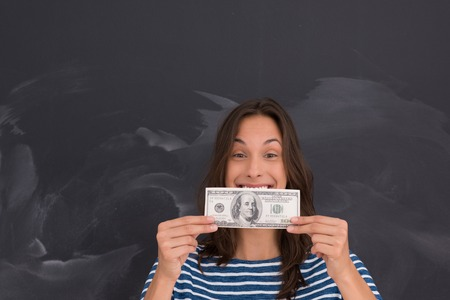 onderwijs: portrait of a young woman holding a banknote in front of chalk drawing board