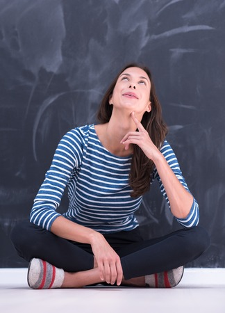 onderwijs: portrait of a young woman sitting in front of chalk drawing board Stockfoto