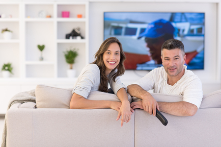 Young couple on the sofa watching television together in their luxury home Stock Photo