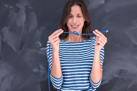 onderwijs: portrait of a young woman holding a internet cable in front of chalk drawing board