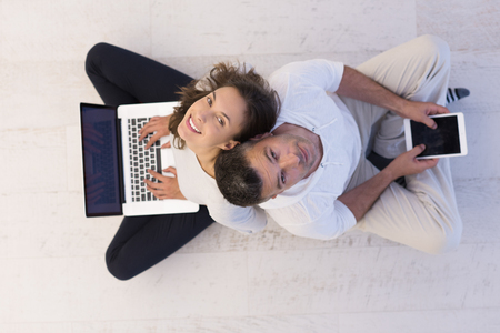 living room: top view of a young couple relaxing at home with tablet and laptop computers reading on the floor Stock Photo