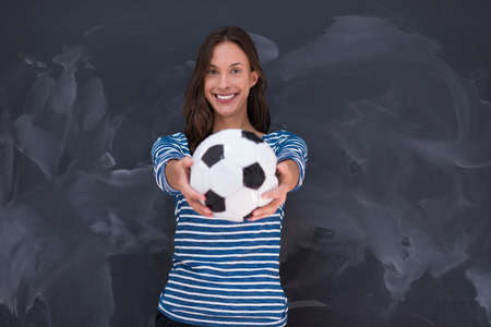 onderwijs: portrait of a young woman holding a soccer ball in front of chalk drawing board