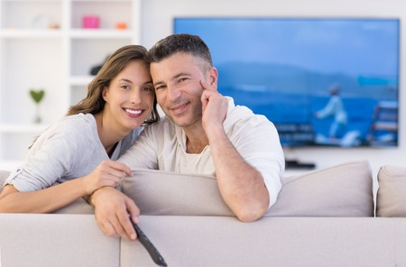 living room: Young couple on the sofa watching television together in their luxury home Stock Photo
