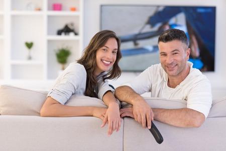 Jong koppel op de bank kijken televisie in hun luxe huis