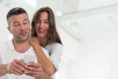 Young happy couple using mobile phone at home together, looking at screen, smiling.